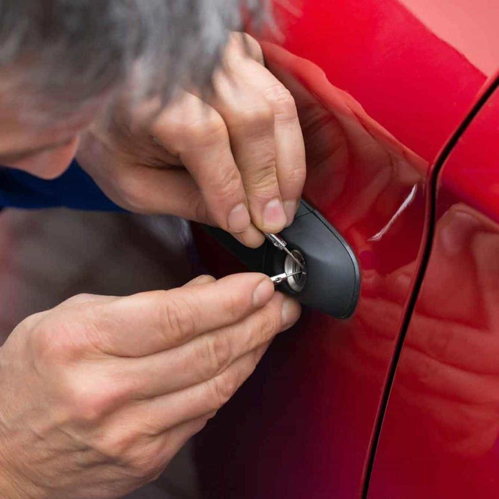 a key trouble locksmith opening a car door for a customer who locked their keys in the car