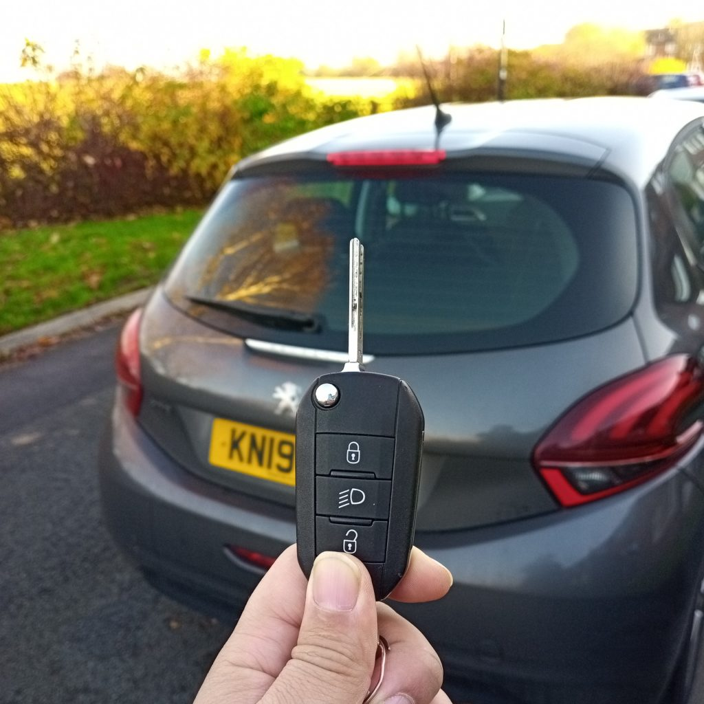 auto locksmith holding up a replacement car key